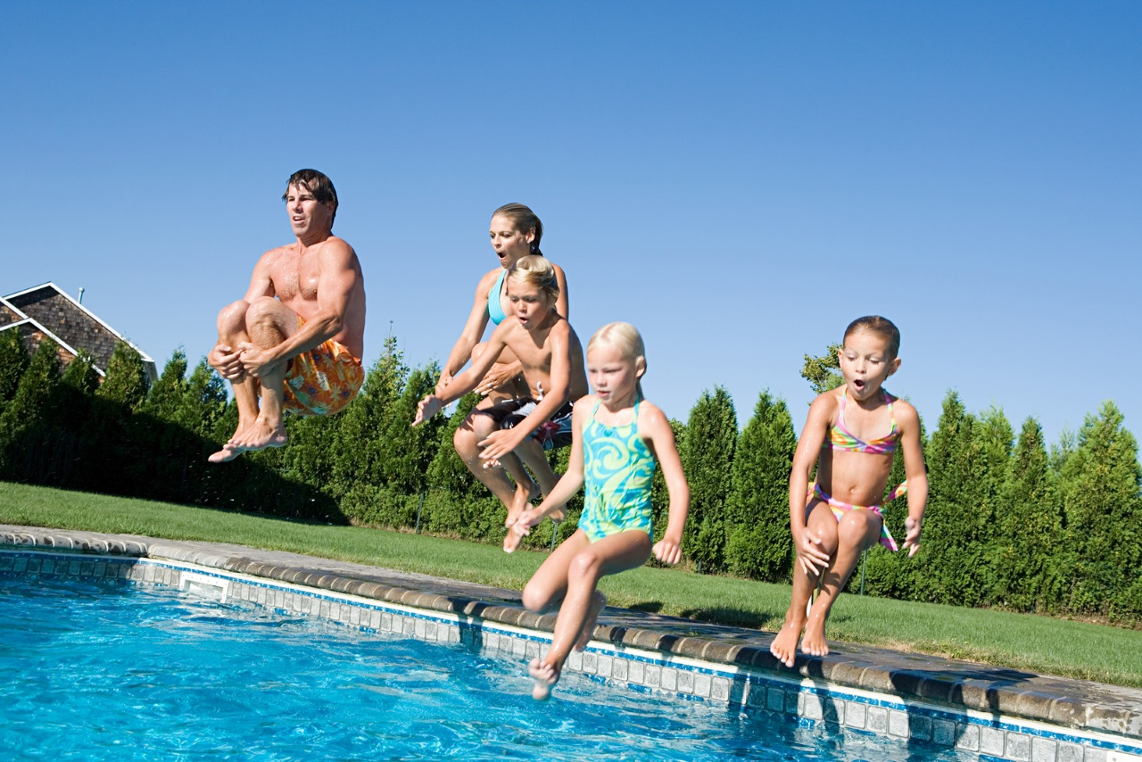 family jumping in pool